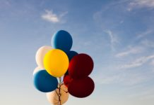 A bundle of multi-coloured balloons against a background of blue sky.