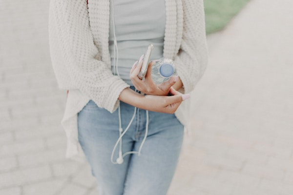 A woman wearing a white cardigan holding a water bottle.