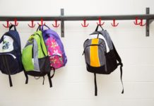 A row of back packs hung up in a school corridor.