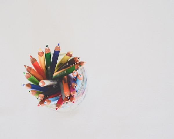 A jar of coloured pencils against a white background.
